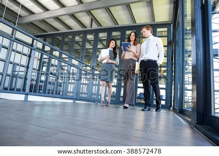 Three confident colleagues discussing in office with documents and digital tablet - stock photo