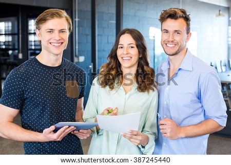 Three confident colleagues discussing in office with documents and tablet - stock photo