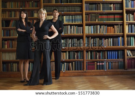 Three confident female lawyers standing in library - stock photo