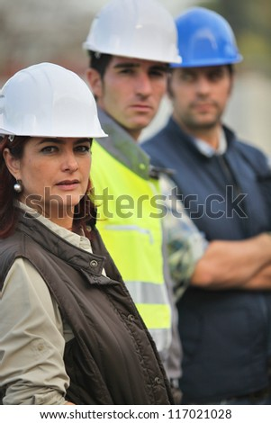 Three construction colleagues stood in a row - stock photo