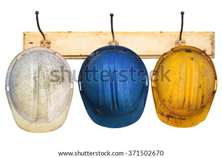 Three construction helmets hanging on a hat-rack isolated on a white background - stock photo