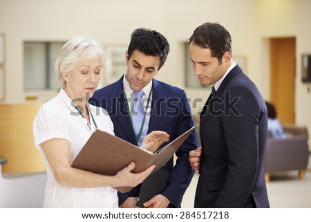 Three Consultants Discussing Patient Notes In Hospital