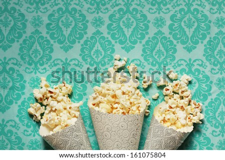Three containers full on popcorn on a turquoise background - stock photo