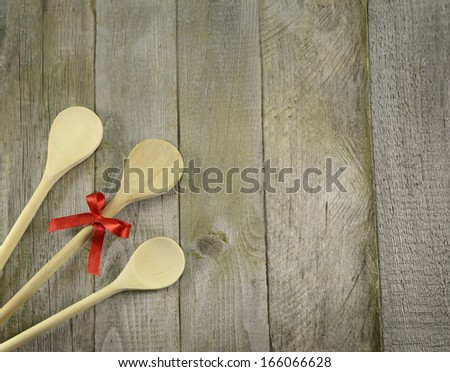 Three cooking spoons on wooden table background - stock photo