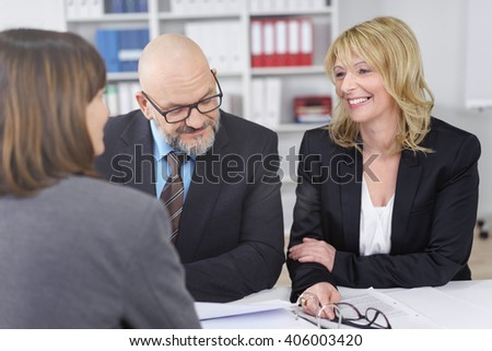 Three corporate executives in a management meeting sitting around a table having a discussion with paperwork in front of them, focus to a smiling woman