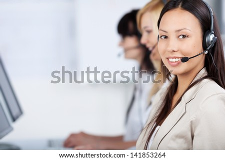 three costumer service executives with headset in the office - stock photo