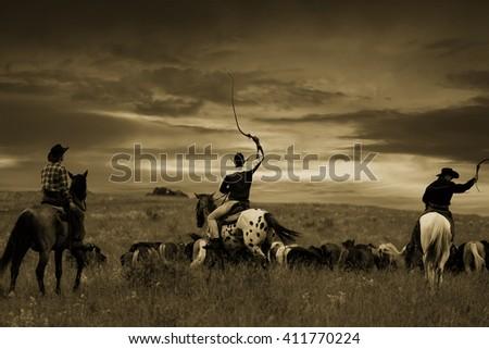 Three cowboys drive herd of horses , toning, vignetting - stock photo