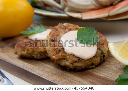 Three crab cakes appetizer with spicy sauce and fresh parsley. Dungeness crab in the background.