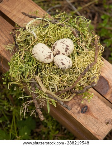 three cream and brown eggs in a birds nest on a wooden crate