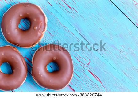 Three crispy cream filled chocolate ring donuts topped with chocolate icing on a rustic turquoise blue wooden background with copy space - stock photo