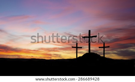 three crosses in silhouette on a hill with sunset - stock photo