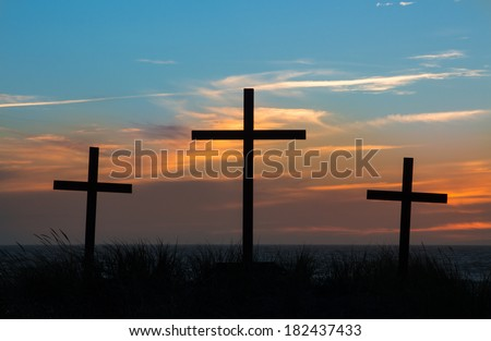 Three crosses with a light clouded sunset behind them.