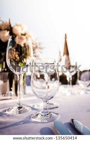 three crystal glasses on a decorative table  with roses and church tower in the background - stock photo