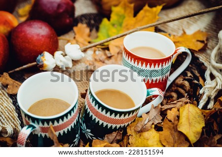 three cup of hot tea and autumn leaves, on a natural fall background - stock photo