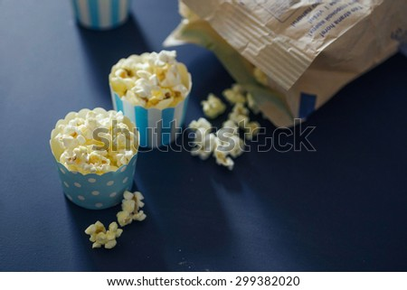 Three cupcake cases filled with salty caramel popcorn on chalkboard background. Fun snack for a children party or a movie night. Selective focus, bokeh, subtle grain and toning.  - stock photo
