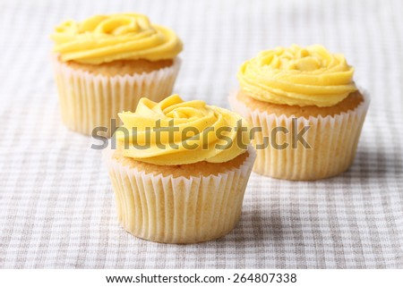 three cupcake frosting with buttercup color buttercream - stock photo