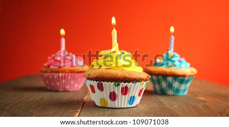 Three cupcake of different colors with birthday candle on a wooden table - stock photo