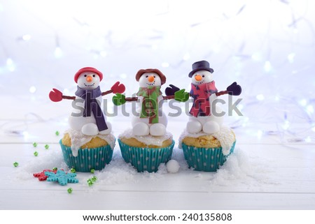 Three cupcakes decorated with sugar snowmen in the snow on a lights background. - stock photo