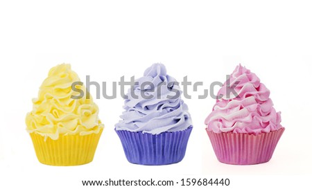Three cupcakes in yellow blue and pink isolated on a white background for cutout