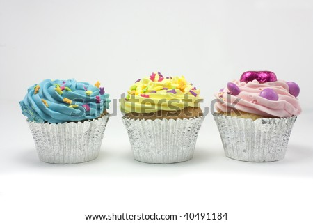 three cupcakes shot on a white background with one candle