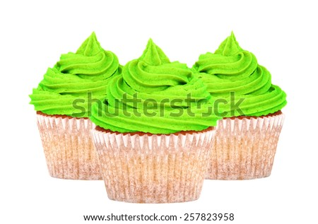 Three cupcakes with bright green frosting for St Patrick's Day, isolated on a white background - stock photo