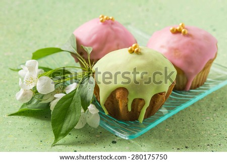 Three cupcakes with pink and green frosting on a glass plate with apple flowers on a green background. Selective focus - stock photo