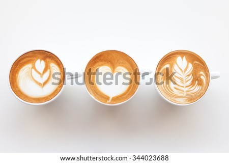Three cups of cafe' latte with three shapes of latte art on white background - stock photo