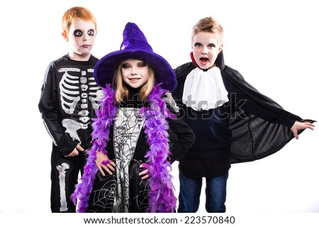 Three cute child dressed the Halloween costumes: witch, skeleton, vampire. Studio portrait isolated over white background    - stock photo