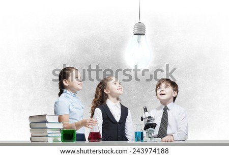 Three cute children at chemistry lesson making experiments - stock photo