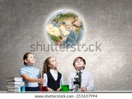 Three cute children at chemistry lesson making experiments. Elements of this image are furnished by NASA - stock photo