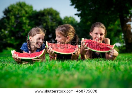 Three cute girls eating watermelon