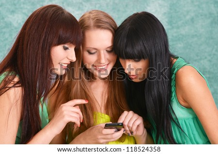 three cute girls in green dresses on a green with a mobile phone - stock photo
