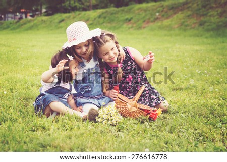 Three cute little girls on picnic in park on sunny summer day. Three little sisters hugging playing outdoors in nature. Horizontal, retouched, filter. - stock photo