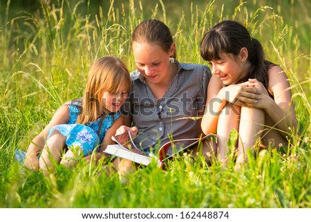 Three cute little girls reading book in natural environment together. - stock photo