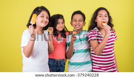 three cute little indian kids eating ice cream, asian girls and boy and ice cream, isolated on green background