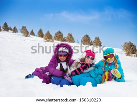 Three cute looking kids girls laying in snow together on sunny day