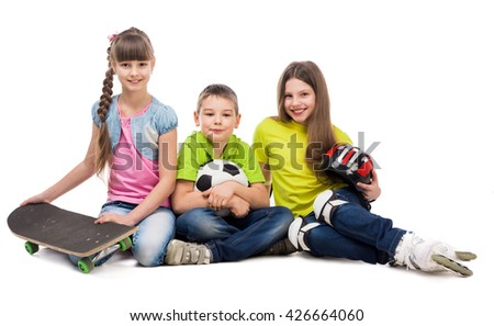 three cute playful children sitting on the floor with sport equipment isolated on white background - stock photo