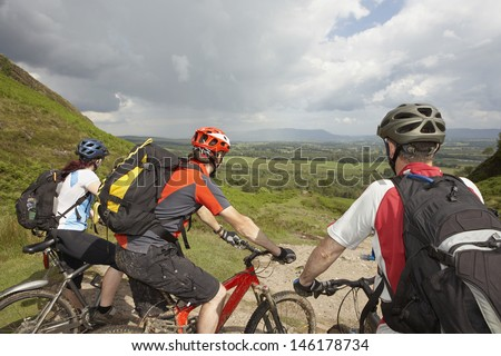 Three cyclists with bikes on track looking at landscape