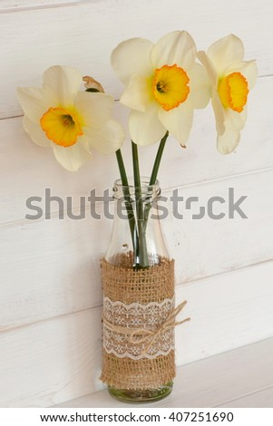 Three daffodils in a vase with water. Wooden background - stock photo