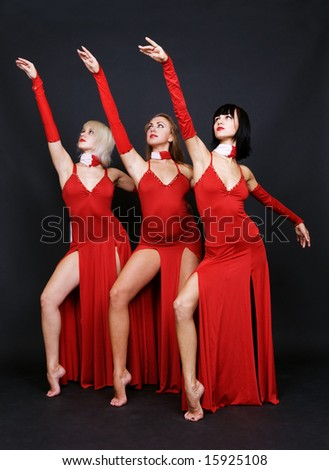 three dancers in red evening gown over dark background - stock photo
