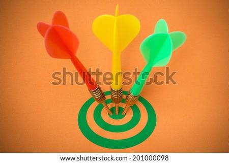 Three darts hitting green target on orange background - stock photo