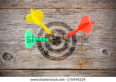 Three darts  hitting target on a wooden planks - stock photo