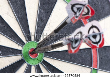 Three darts in bulls eye of dartboard with shallow depth of field concept for hitting target - stock photo