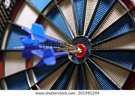 Three darts in bulls-eye, shallow depth of field, focus on bullseye