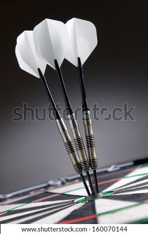 Three darts in bullseye of dartboard - stock photo