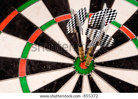 Three darts in the bullseye. Checkered fletchings in focus.