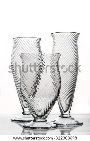 three decorative glasses on a mirrored desk  - stock photo