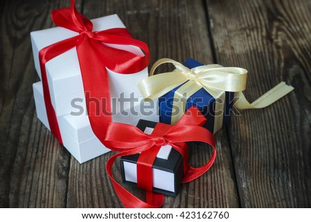 Three decorative multicolored gift boxes with ribbons on a rustic wooden background. Holiday concept