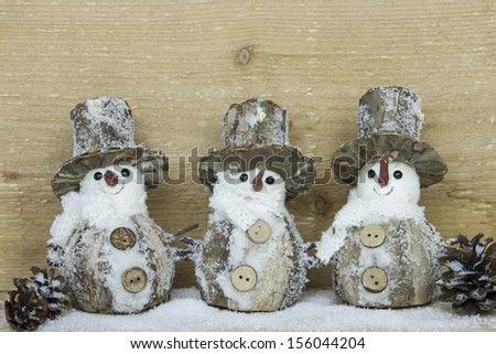 three decorative snowman with snow and pine cones - stock photo