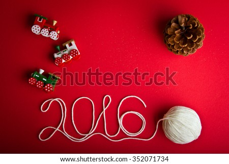 Three decorative toy trains, one pine cone and white ball of yarn on hot red background. Christmas and 2016 New Year theme. Place for your text, wishes, logo. - stock photo